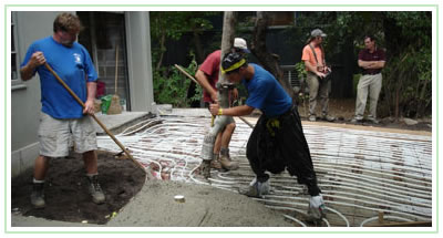 Pouring concrete over heating coils in a client's driveway.